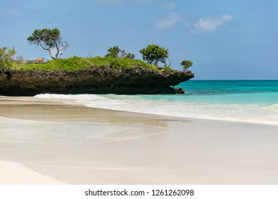 A rocky outcrop with trees on juts out next to a beach and the Indian ocean, Kenya