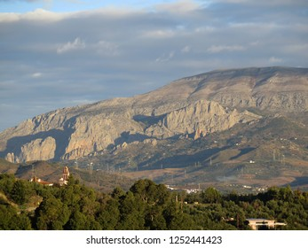 Rocky outcrop viewed over convent belfry in Andalusian countryside