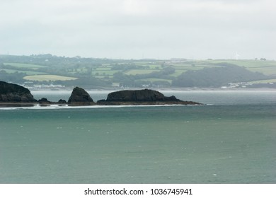 A rocky outcropping jutting into the sea with coastline behind