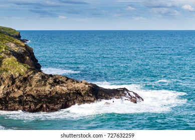 Rocky outcrops lead into an azure sea under a bright sky with light fluffy clouds