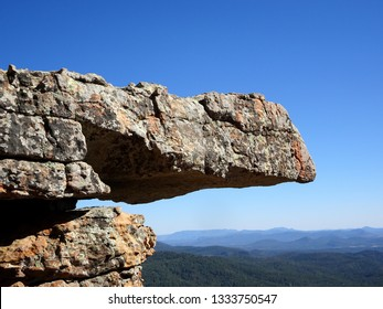 A rocky overhang against a blue sky over distant mountains;  Mogollon Rim in Apache-Sitgreaves National Forest in Arizona