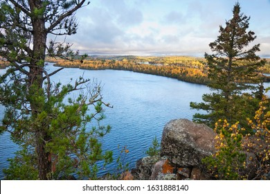 Rocky overlook of northern Minnesota lake with pines and birch in fall color