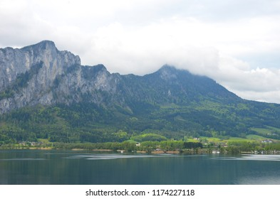 The rocky peaks of a mountain are surrounded by cloud. The lower slopes are covered with forest. A small village nestles along the edge of the river.