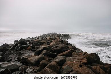 Rocky pier in pacific ocean. Pacific Northwest. Rocky breakwater. Birds resting on the breakwater.  - Shutterstock ID 1676585998