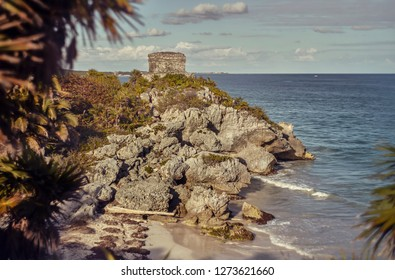 Rocky promontory overlooking the Caribbean Sea with an ancient Mayan building on top: Watchtower of the Mayan complex of Tulum in Mexico.