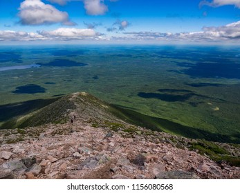 A rocky ridge leads down into a lush expansive valley, along the slopes of Katahdin's Helon Taylor trail in Baxter State Park, Maine.