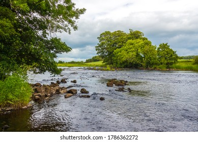 A rocky riffle under trees on a summers day on the River Dee, Galloway, Scotland