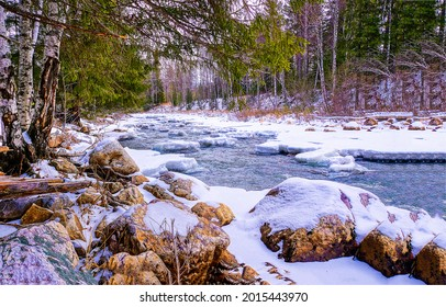Rocky river bank in the snow. Winter forest river snow. Snowy river in winter forest. Winter forest river snow