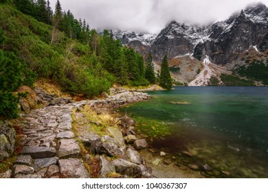 Rocky road along the shore of a mountain lake in High Tatras in autumn.