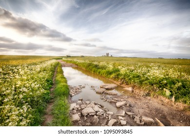 Rocky road flooded in a rural landscape leading to a ruin of a church in Norfolk England