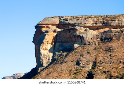 A rocky sandstone mountain jutting out on a blue sky background