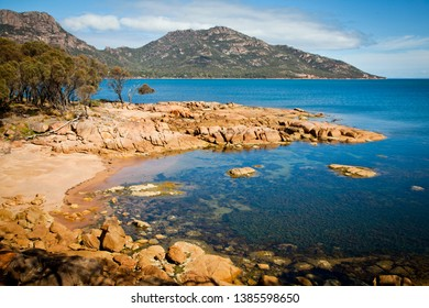 Rocky sandy beach and crystal clear water with mountain backdrop. Coles Bay Conservation Area with Mount Amos in Freycinet National Park in background. East coast Tasmania.