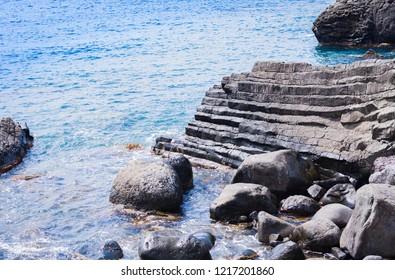 Rocky sea shore of Acitrezza next to Cyclops islands and Acicastello, Catania, Sicily, Italy