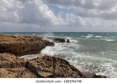 Rocky sea shore with splaches of waves. Cyprus - Mediterranean Sea coast.