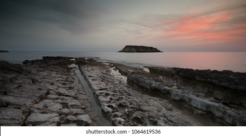Rocky Seascape at dramatic sunset with the small  island of Geronisos st.  Georges cape at Paphos area Akamas peninsula in Cyprus