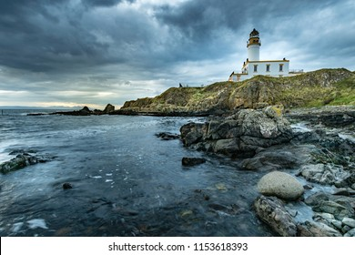 Rocky seascape at Turnberry point lighthouse with cloudy moody sky  at coast line