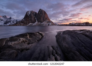 Rocky seashore with mountain range in the background, Lofoten, Norway