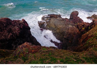 Rocky Seashore at Port Macquarie Australia. White crested waves crashing on jagged rocks at the Lighthouse Beach.