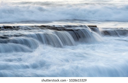 Rocky seashore with wavy ocean and waves crashing on the rocks at Akrotiri coast area in Limassol, Cyprus