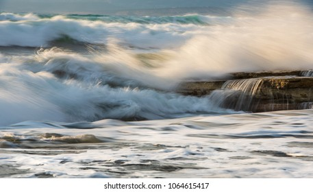 Rocky seashore with wavy ocean and wind waves crashing on the rocks at Akrotiri coast area in Limassol, Cyprus