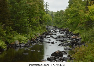 Rocky section of Peshekee River bordered by trees in Upper Peninsula of Michigan
