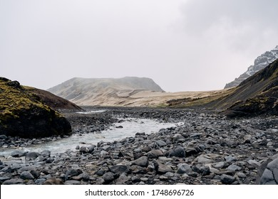 Rocky shallow mountain river in Iceland, flows against the backdrop of mountains.