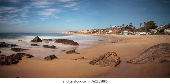 Rocky shore with Beach cottages lining Crystal Cove State Park beach, right on the sand with an ocean view in Newport Beach, California