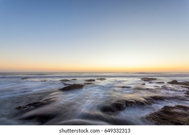 A rocky shore with blurred water at sunset