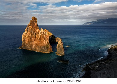 Rocky shore of the coast of Madeira island. Dramatic seascape, alone steep reef, lit by evening sun against deep blue ocean and cloudy sky. In october near Porto Moniz, Madeira.