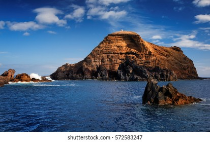 Rocky shore of the coast of Madeira island. Dramatic seascape. deep blue ocean with orange colored cliffs. Blue sky with few clouds. Porto Moniz in october, Madeira Seascape.