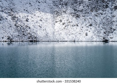Rocky shore of Gokyo lake covered with snow, Everest region, Nepal