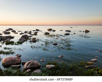 Rocky shore of Gulf of Finland in front of bright and peaceful sunset colors