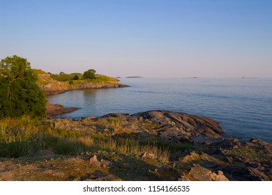 The rocky shore of the historic fort on the island of Suomenlinna in the Gulf of Finland is illuminated by the evening sun. Finland, Suomenlinna.