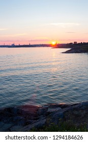 The rocky shore of the island of Suomenlinna, and the view of the Gulf of Finland and the sunset on a quiet summer evening in Finland. Beautiful nature of Finland.