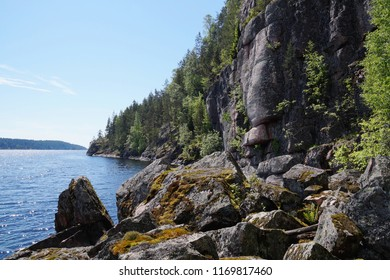 Rocky shore of lake Ladoga, rock, overgrown with forest, in the Bay of Ladoga, rocks covered with mosses.