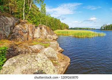 Rocky shore in Mon Repos Park in city Vyborg, Vyborg Bay, Russia. Blue  sky and blue water, beautiful landscape in park.