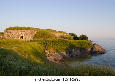The rocky shore and the old fortifications of the historic fort on the island of Suomenlinna in the Gulf of Finland illuminate the evening sun. Finland, Suomenlinna, summer sunset.