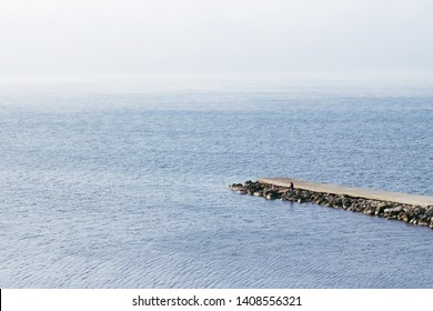 The rocky shore of the sea. Autumn cold weather. Sea view from above. Nature background. Stone pier in the sea