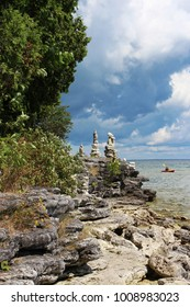 The rocky shoreline of Lake Michigan with cairns and a kayaker in the distance in Cave Point County Park, Sturgeon Bay, Wisconsin, USA
