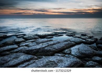 Rocky shoreline of Lake Ontario during sunset near Cobourg, Ontario