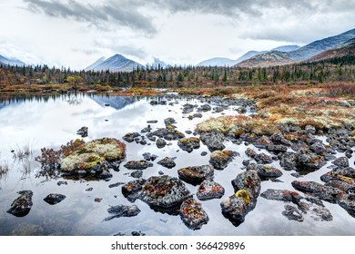 Rocky side of a Polygonal lake in tundra of Kunijok valley in Hibiny mountains above the Arctic circle, Russia