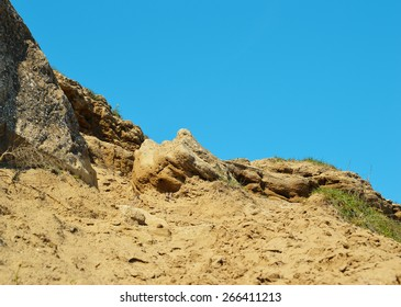 Rocky slope with trodden sand road