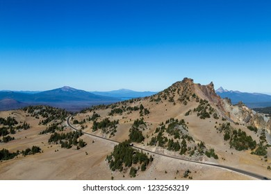 rocky spires and crumbling rocks at the top of Crater Lake with Mount Thielsen in the background