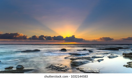 Rocky Sunrise Seascape with Sun Rays - Capturing the sunrise from Toowoon Bay Beach on the Central Coast, NSW, Australia.