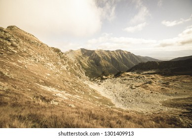 rocky Tatra mountain tourist hiking trails under blue sky and occasional mist  cloud in Slovakia, path to Volovec mountain - vintage retro look