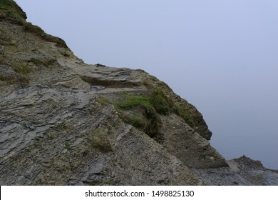Rocky Textured Layered Cliff Mountain Edge Overlooking Overcast Foggy Blue Ocean Sea with Coastal Green Grass, Loose Rock, Sedimentary Basin Rock and Flagstone
