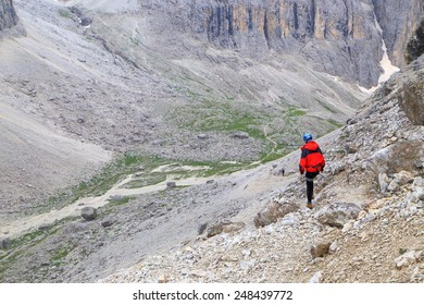 Rocky trail along Lasties Valley and distant climber descending towards bottom, Sella massif, Dolomite Alps, Italy