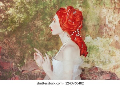 Rococo redhead princess with perming hairstyle. Fabulous ancient queen with historic hairdo against backdrop of stone wall. Rococo doll. Ancient princess in historic palace. Perming hairstyle.
