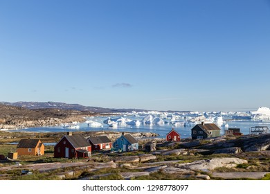 Rodebay, Greenland - July 09, 2018: Colorful wooden houses with icebergs in the background. Rodebay, also known as Oqaatsut is a fishing settlement north of Ilulissat.
