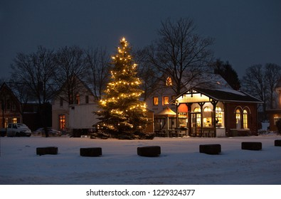 Rodenkirchen, Germany - January 05, 2016: enlightened christmas tree on the market square in front of a fast food restaurant on a sceny snowy evening
